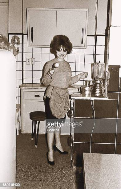 vintage photo of a young woman in the kitchen - archival stock pictures, royalty-free photos & images
