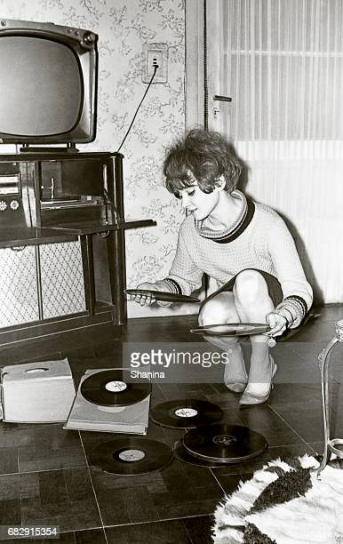 vintage photo of a young woman looking at vinyl records - film d'archive photos et images de collection