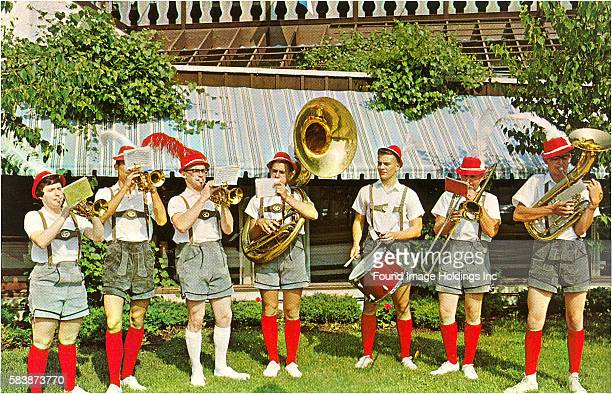 Vintage photograph of a brass band dressed in Tyrolean outfits and playing their instruments outside in the 1960s.