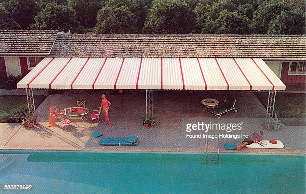 Vintage photograph of a couple in their suburban backyard featuring a large red and white metal awning and a swimming pool in the 1960s