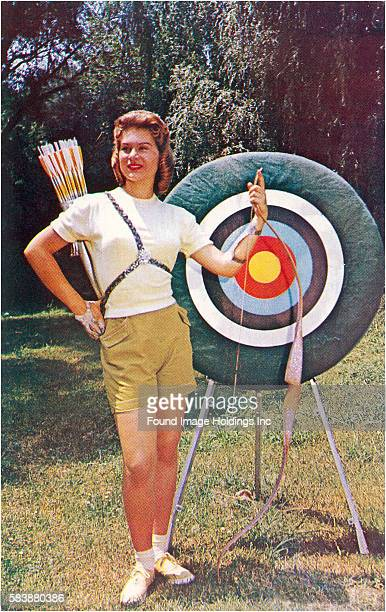 Vintage photograph of a female archer standing outside next to a bullseye target, holding her bow, and wearing a quiver full of arrows in the 1960s.