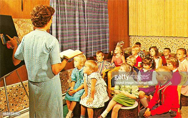 Vintage photograph of a female teacher giving a lesson to young children in an elementary school classroom in the 1960s.