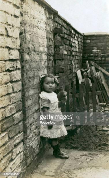 Vintage photograph of a little girl holding a teddy bear in her back garden near Manchester, England circa 1909.