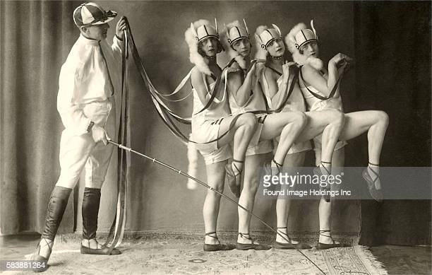 Vintage photograph of a man in jockey attire holding a riding crop and the ribbon reins of four young women costumed as a team of horses 1910s