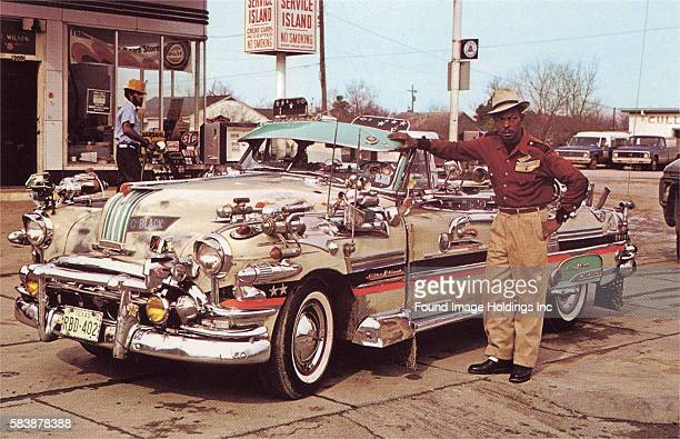 Vintage photograph of a man standing next to his KlaxonLoaded Car in the 1960s non