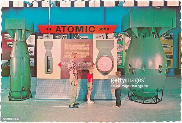 Vintage photograph of a man with two young boys in a museum looking at the display of two atomic bombs next to a diagram explaining how they work...