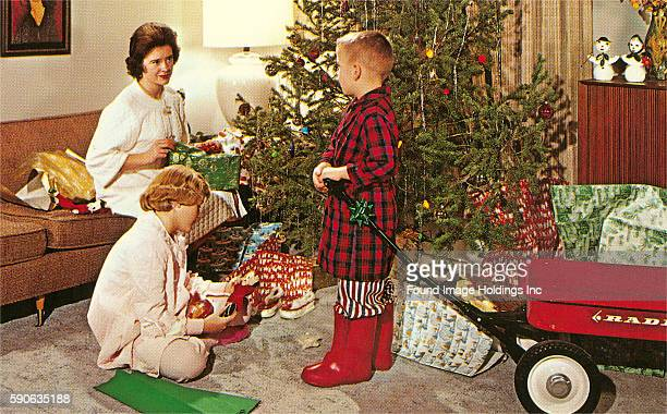 Vintage photograph of a mother daughter and son in front of a Christmas tree on Christmas morning opening presents beside a red Radio Flyer wagon...