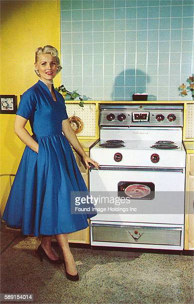 Vintage photograph of a smiling blonde woman wearing a blue dress showing off her stove and kitchen 1950s