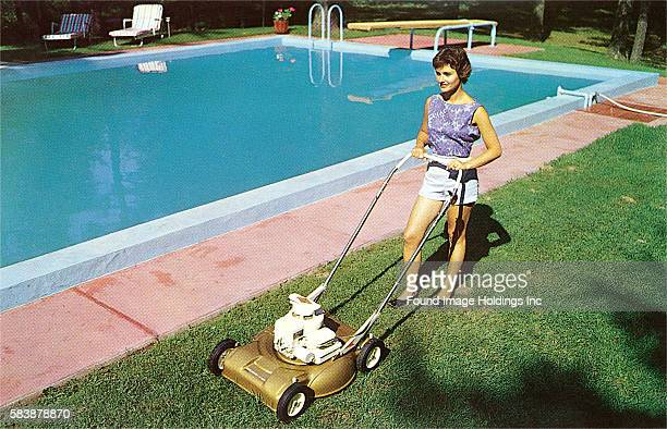Vintage photograph of a woman in shorts and a sleeveless blouse pushing a gas powered lawn mover in a suburban backyard next to a swimming pool in...