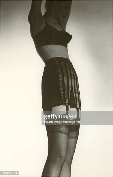Vintage photograph of a woman with her arms up wearing a bra girdle garters and stockings for an advertisement 1940s