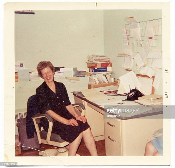 Vintage photograph of an happy secretary sitting at her desk