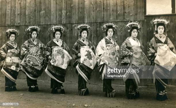 Vintage photograph of seven geishas posing on a Tokyo street, c. 1915. Toned silver print.