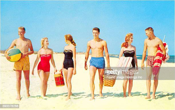 Vintage photograph of three young couples wearing bathing suits, carrying picnic supplies and a beach ball, in the sand at an ocean beach, 1950s.