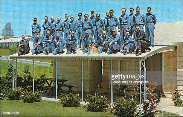 Vintage photograph of twentysix workmen wearing blue uniforms while posing on a suburban patio roof in the 1960s