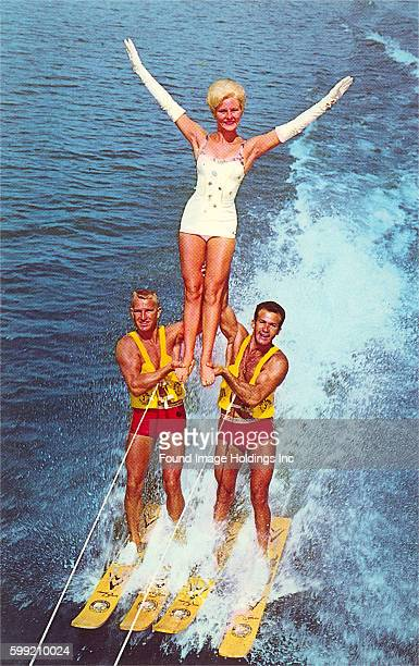 Vintage photograph of two men waterskiing while supporting a standing woman wearing long white gloves and a white bathing suit in the 1960s