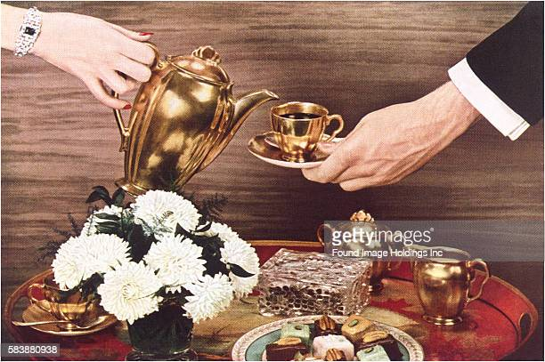 Vintage photograph of woman's hand pouring coffee from a gold pitcher into a gold cup and saucer held by a man's hand above a tray with flowers and...