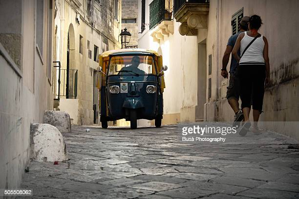 A vintage Piaggio Ape minivan in the alleys of the historic center of Otranto, Apulia, Southern Italy