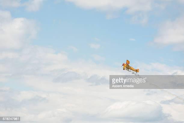 vintage plane creates pattern in big sky - 航空ショー ストックフォトと画像