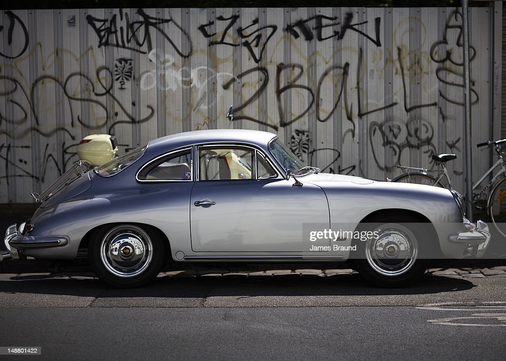 Vintage Porcshe against wall of graffiti. : Stock Photo
