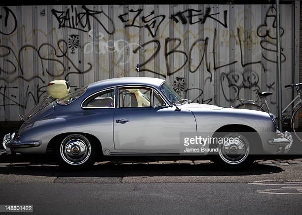 vintage porcshe against wall of graffiti. - porsche stock-fotos und bilder