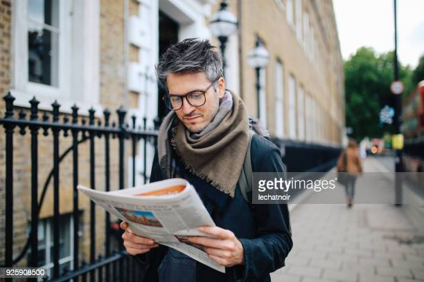 vintage portrait of a man reading newspapers in london downtown - newspaper stock pictures, royalty-free photos & images