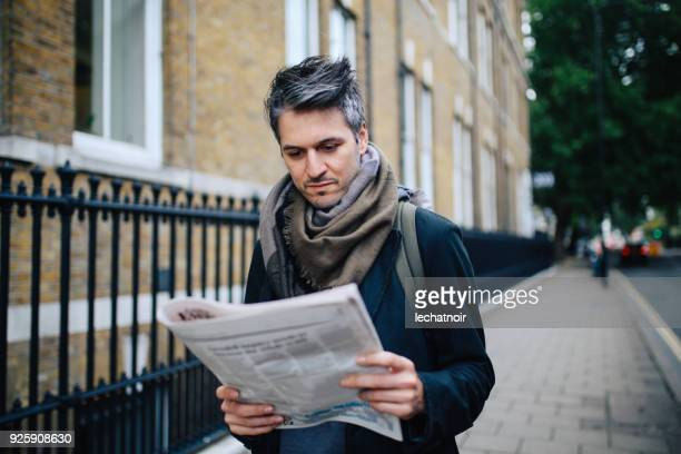 vintage portrait of a man reading newspapers in london downtown - magazine stock pictures, royalty-free photos & images