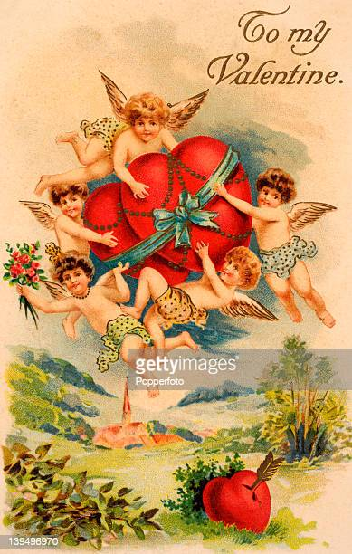 A vintage postcard celebrating St Valentine's Day with a host of cherubs or baby angels conveying a giftwrapped heart across an English countryside...