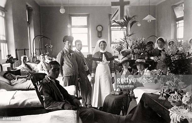 A vintage postcard featuring a busy hospital ward including patients visitors and nursing staff with bouquets of flowers during World War One circa...