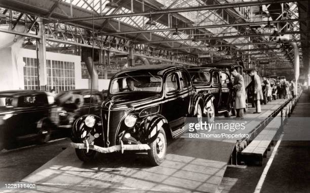 Vintage postcard featuring a car assembly line at a factory in Dagenham in Essex, circa 1930.
