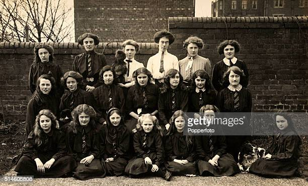A vintage postcard featuring a class photograph of young girls with their teachers circa 1905