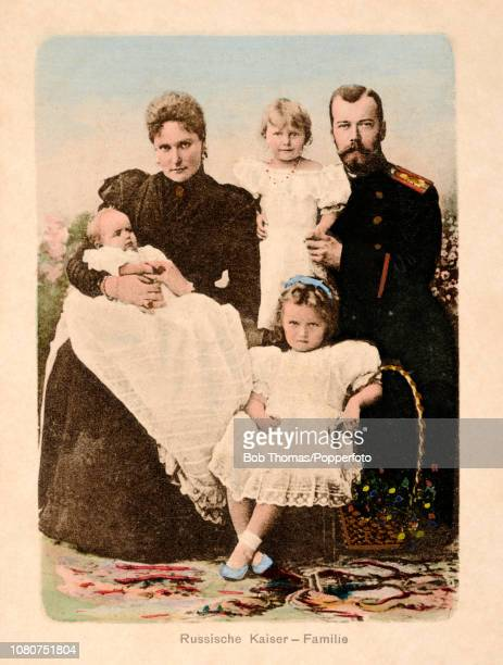 A vintage postcard featuring a colour photograph of Czar Nicholas II and Czarina Alexandra of Russia and three of their five children left to right...