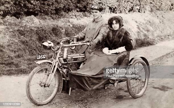 Vintage postcard featuring a couple riding in their Grey Goblin motorcycle, she in a sidecar, circa 1920.