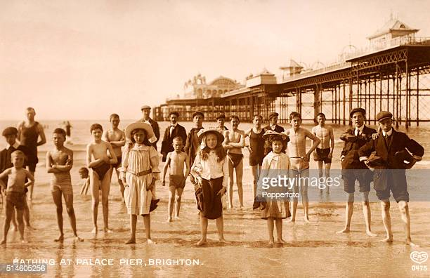 Vintage postcard featuring a group of holidaymakers on the beach at the Palace Pier in Brighton, circa 1911.