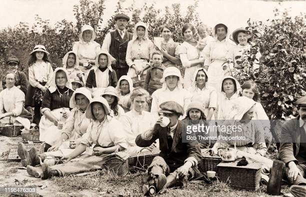 Vintage postcard featuring a group of people, mostly women, enjoying a Sunday outing picnic, circa 1910.