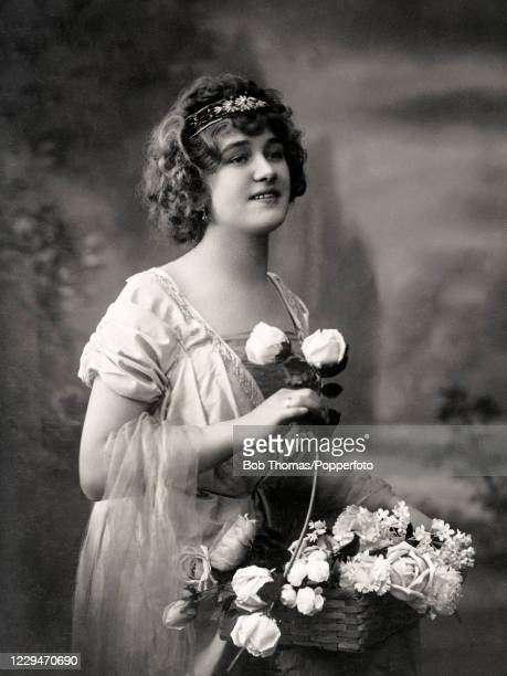 Vintage postcard featuring a studio portrait of a stylishly-dressed young lady with a basket of flowers, circa 1910.
