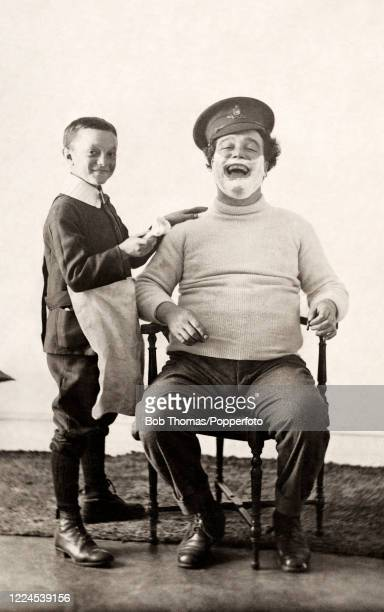 Vintage postcard featuring a studio portrait of a young boy holding a shaving brush whilst applying shaving creme to his laughing father who wears a...