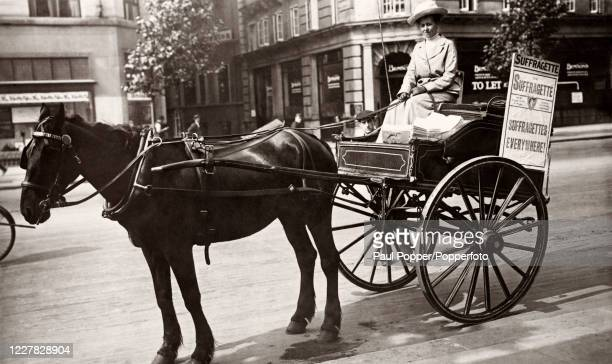 Vintage postcard featuring a suffragette driving her horse and carriage in London, circa 1912.