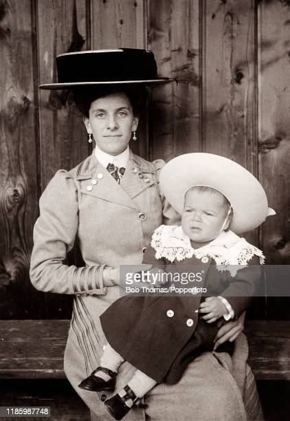 A vintage postcard featuring a woman wearing a large broadberibboned hat with a young child on her lap in their Sunday best clothes circa 1910
