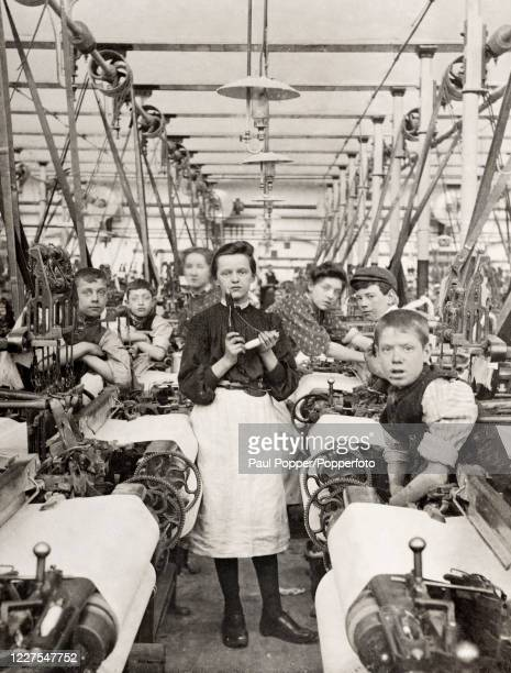 Vintage postcard featuring factory workers in a cotton weaving shed in Burnley, Lancashire, circa 1910.