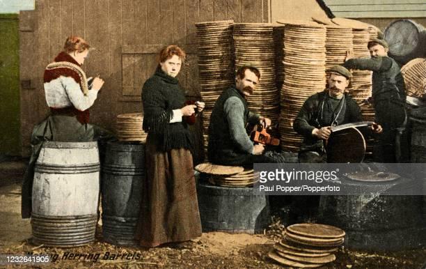 Vintage postcard featuring men and women making herring barrels at Lowestoft, Suffolk, circa 1906.