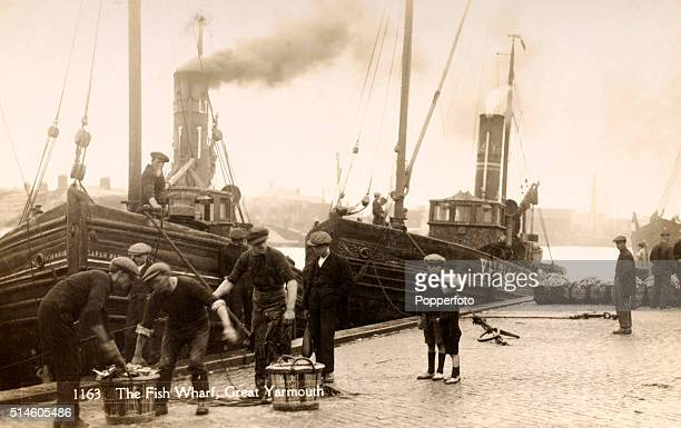A vintage postcard featuring the Fishing Wharf at Great Yarmouth with little boys watching the fishermen unloading their catch circa 1910