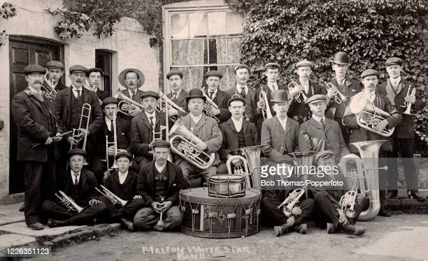 Vintage postcard featuring the men and boys of the Malton White Star Brass Band with drums in North Yorkshire, circa 1910.
