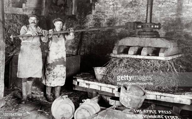 Vintage postcard featuring two men operating a cider large apple press whilst making Devonshire Cider, circa 1920.