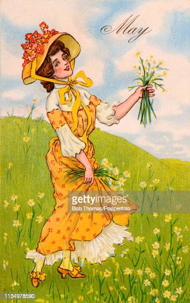 Vintage postcard illustration depicting the month of May with a young lady in a large flowered hat picking wildflowers on a hillside with fluffy...