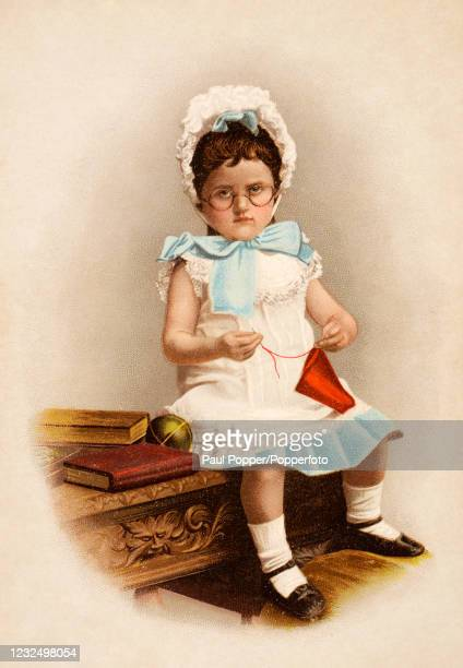 Vintage postcard illustration featuring a little girl wearing spectacles with books and Christmas ornaments, circa 1900.