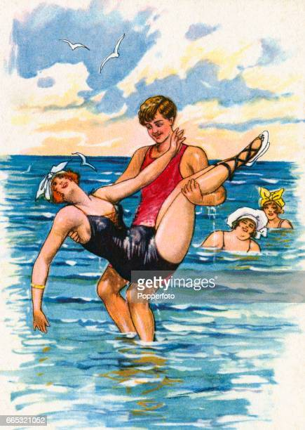 A vintage postcard illustration featuring a seaside scene with a young man lifting a buxom young lady as two bathing beauties look on circa 1900