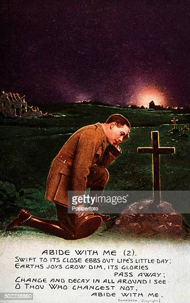 A vintage postcard illustration featuring a soldier kneeling beside a war grave at sunset and the words to the hymn Abide with Me during World War...