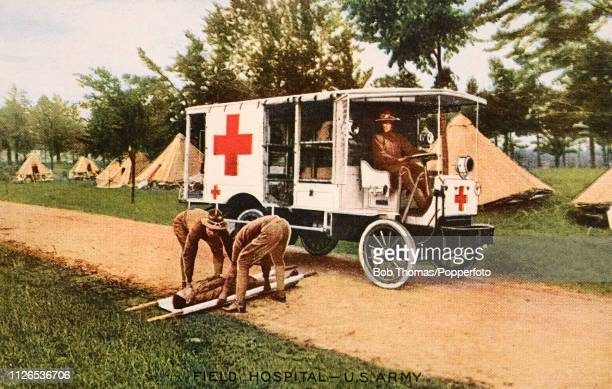A vintage postcard illustration featuring motorised transport emblasoned with large red crosses used by the US Army in their field hospitals during...