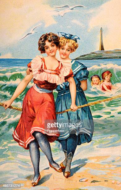 A vintage postcard illustration featuring two young ladies in swimming costumes larking about holding onto a rope at the seaside circa 1912
