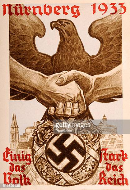 A vintage postcard illustration of German nationalistic propaganda featuring the German eagle two clasped hands the Nazi swastika and a cityscape of...
